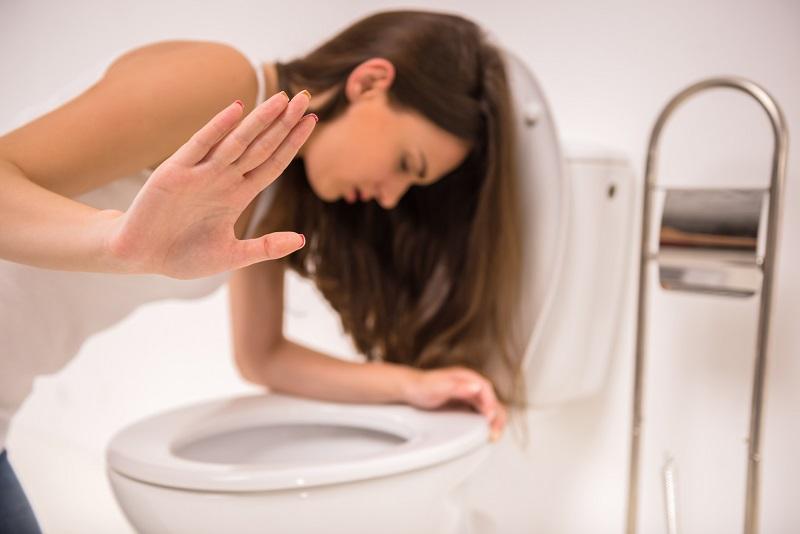 Nevoľnosť a zvracanie v tehotenstve, žena nad toaletou, napína ju na vracanie