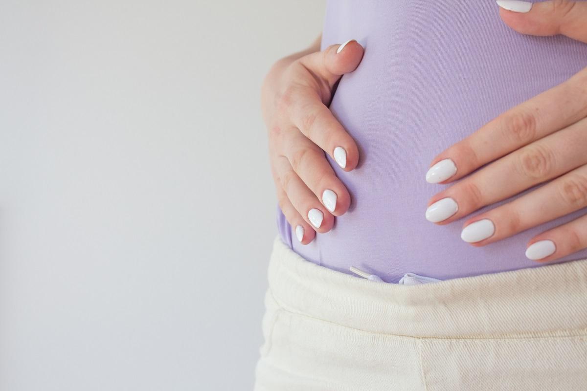 Nafukovanie v tehotenstve. Žena si drží brucho rukami