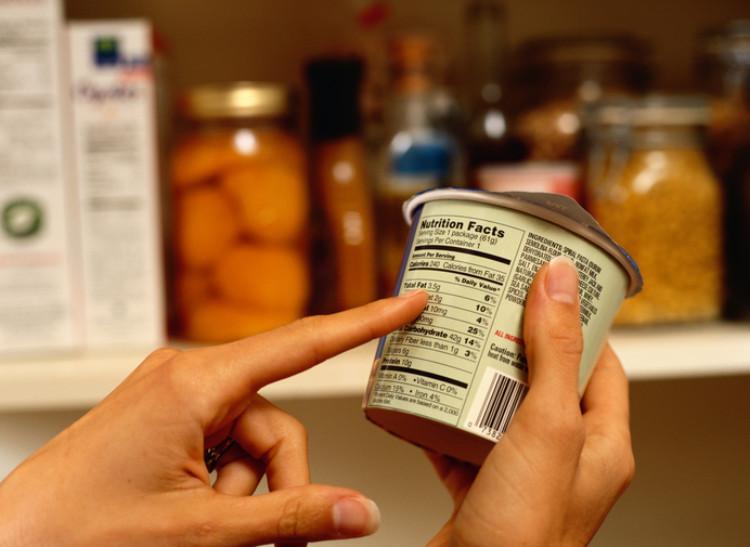 ruka držiaca kelínok s jedlom pozerá sa na dátum spotreby