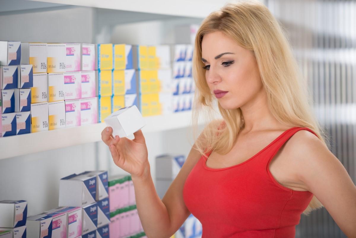Žena si vyberá lieky v lekárni pri výklade s krabičkami liekov